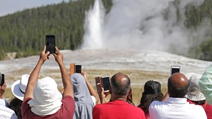 Visitors hold up their cellphones to take pictures of an erupting geyser.