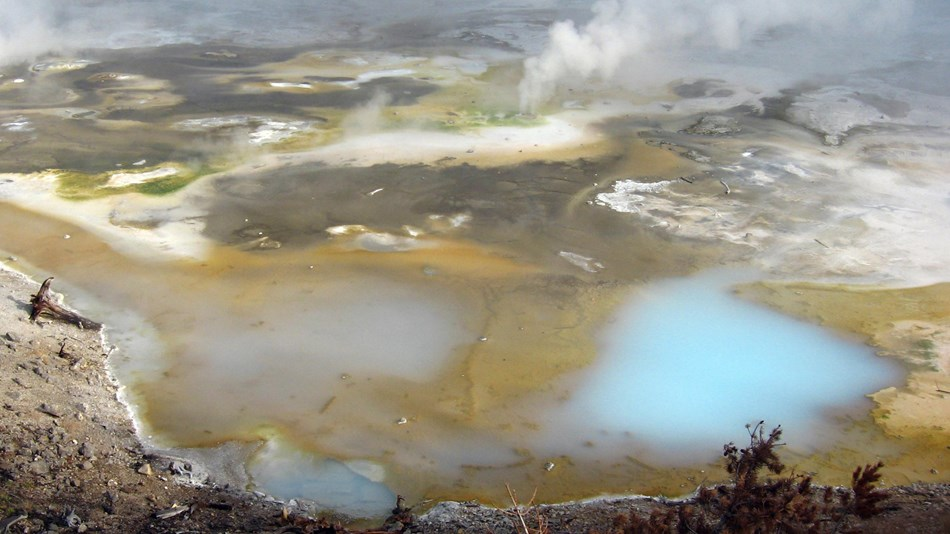 Multi-colored ground dotted with milky blue pools and rising steam.