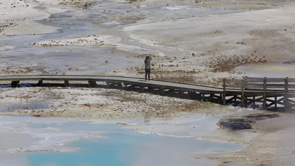 A lone person standing on a boardwalk and takes a picture of steaming hot springs.