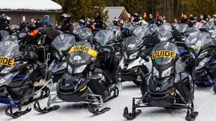 Snowmobiles parked in lines near a set of buildings.