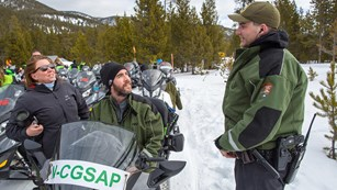Visitors on a snowmobile talk with a park ranger