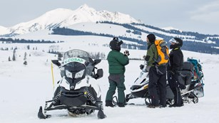 Snowmobilers stop to take photos of Electric Peak at a Swan Lake Flats pull-out.