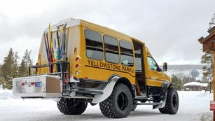 A snowcoach is loaded up with skis at Old Faithful for a day of cross-country skiing.