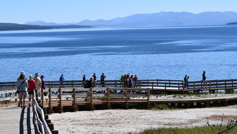 Visitors walking along the West Thumb Geyser Basin boardwalk.