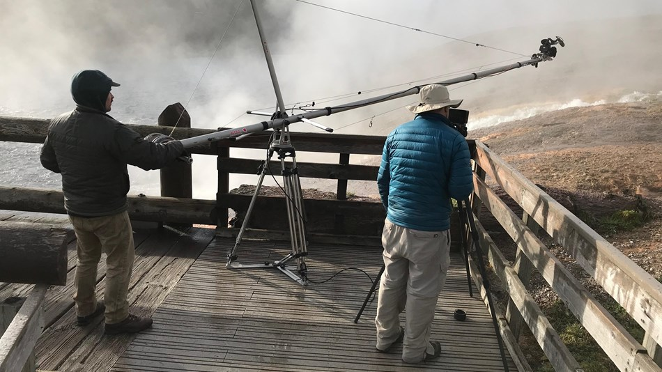 Two people controlling a jib from the boardwalk to collect video footage.