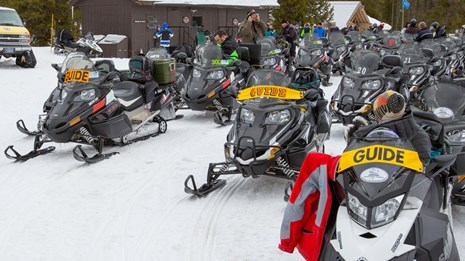 Three lines of snowmobiles wait for their drivers to return.