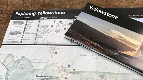 A brochure with the word Yellowstone sits on top of another unfolded brochure.