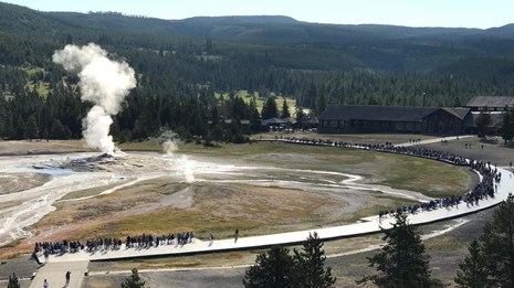 View from the top of a building shows visitors standing in a wide arc around a steaming geyser.