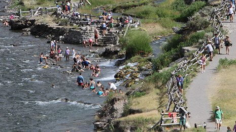 Visitors enjoying the thermally-heated waters where the Boiling River enters the Gardiner River.