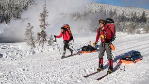 Two skiers traveling across a wide trail with backpacks to ski-sleds.