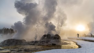 A skier enjoys a winter sunrise at near a steaming geyser.