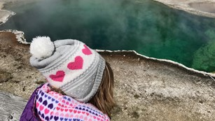 Child wearing a winter hat and coat looking out across a deep, aqua-green hot spring.