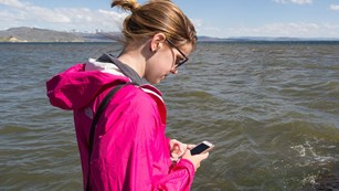 Someone using a cell phone by Yellowstone Lake.