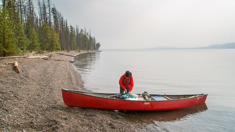A person unloading a canoe on the shore of Yellowstone Lake.