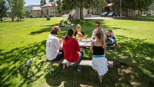 A family sits around a picnic table and enjoys a meal together.