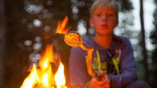 A camper toasts a marshmallow over an open fire
