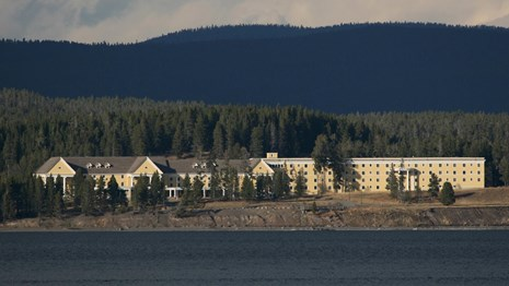 Yellow and white Lake Hotel sitting near the shore of Yellowstone Lake