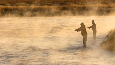 Two anglers standing in the water and fly-fishing during the golden light of dawn.