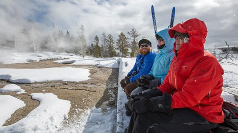 People bundled up while waiting for an eruption of a geyser.