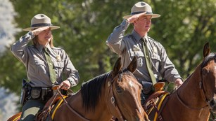 Two rangers on horseback salute during a ceremony.