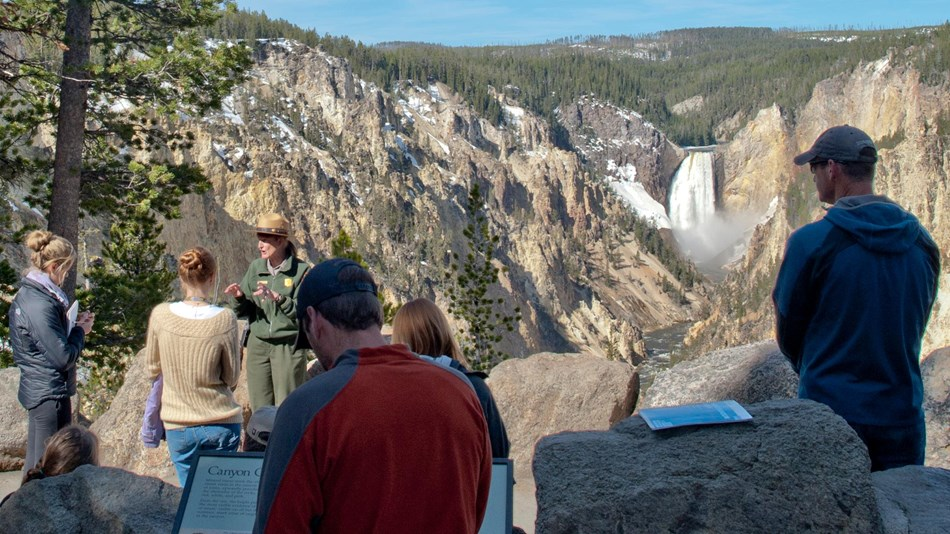 Ranger talking to a group of people with the Lower Falls in the background.