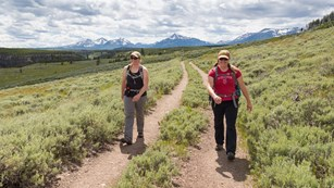 Two women walking on a trail with mountains in the landscape in the background.