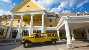 An old-fashioned yellow and black bus is parked in front of a tall, yellow inn with white columns.