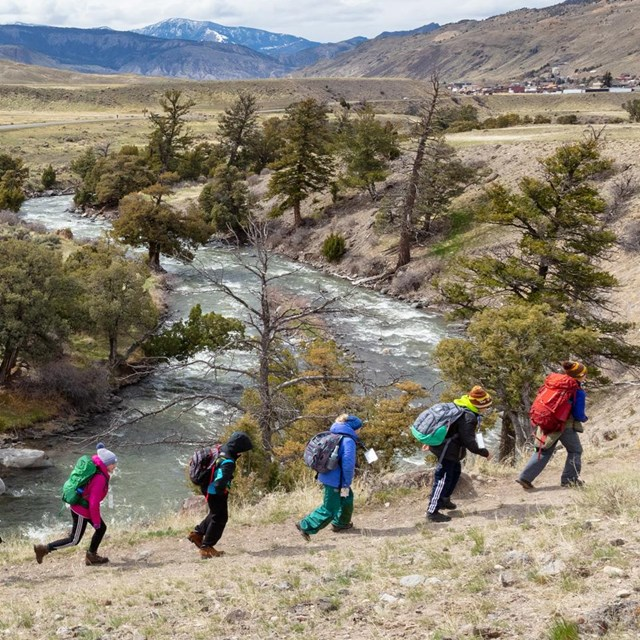 Students hike along a trail near a river.