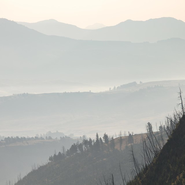 Smoke obscures the valleys and mountains in a wilderness landscape
