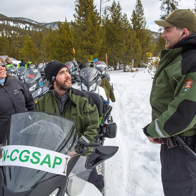 Visitors on a snowmobile talk with park ranger