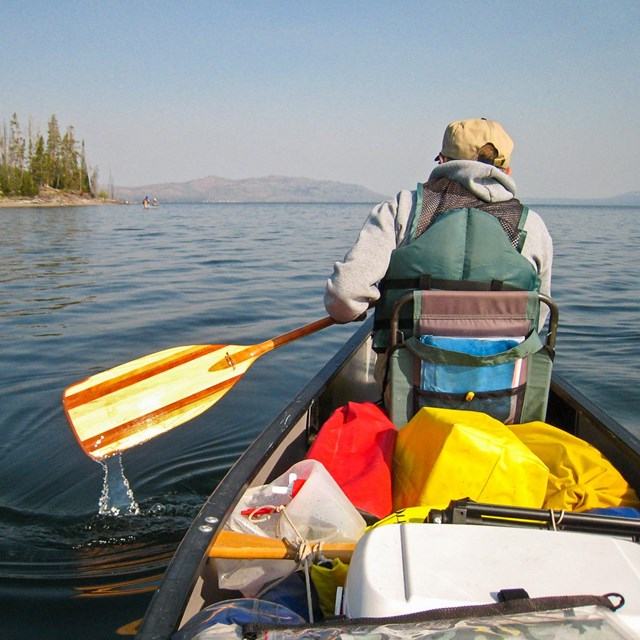 Canoer paddles on Yellowstone Lake