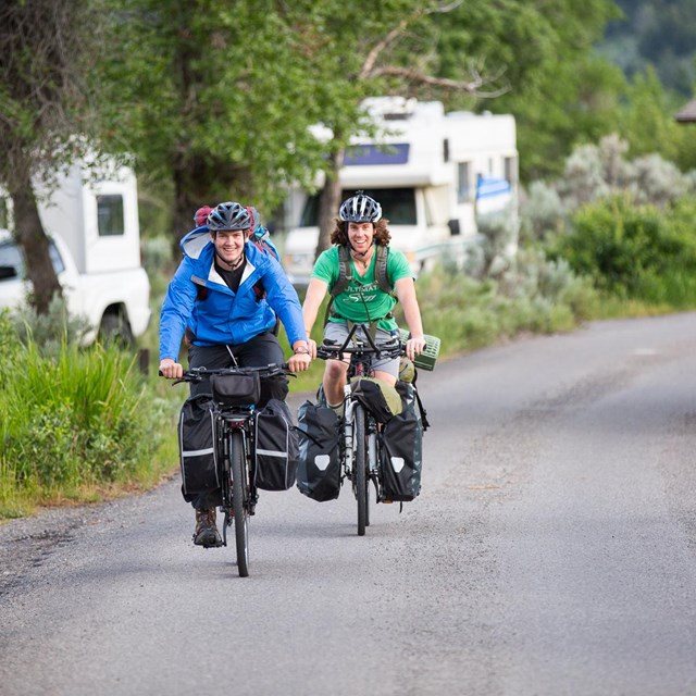 Cyclists pedal around a campground