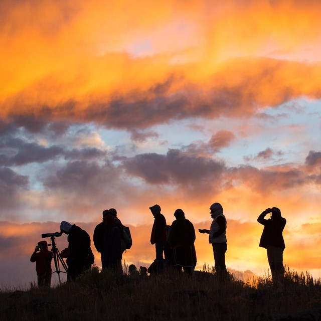 A group of people gather during sunrise