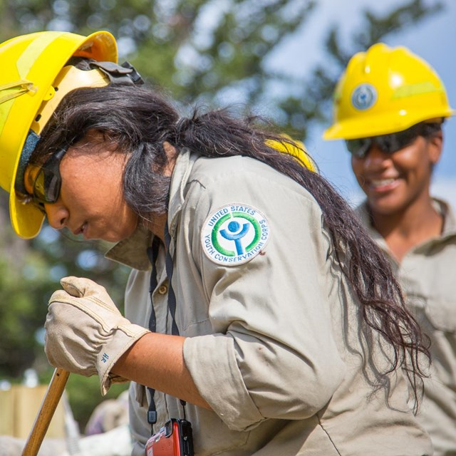 Photo Youth Conservation Corps members repairing a fence.