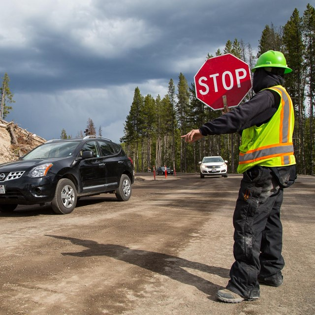 A flagger guides cars through road construction.
