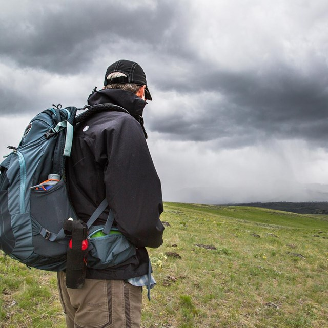 A hiker watches an approaching storm on Specimen Ridge