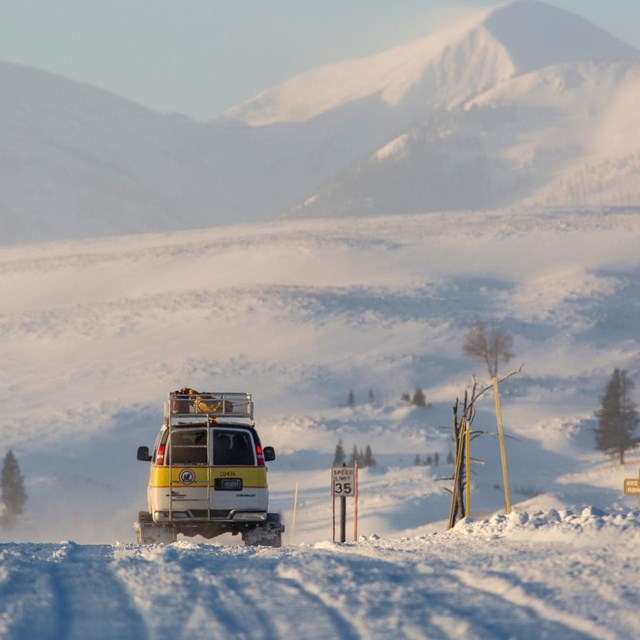 A snowcoach on winter road.