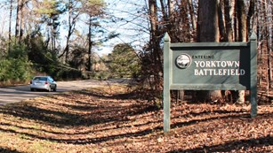 Car driving Colonial Parkway past sign that says,