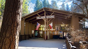 Exterior view of store entrance with large wood pillars and peaked roof, surrounded by trees.