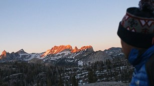 A hiker in warm jacket and hat overlooks high country scenery at sunset