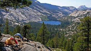 Two tents and campers overlook the high country, with Half Dome and a lake in the background.