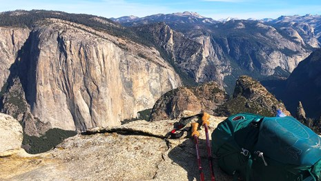 A backpack and trekking poles sit on a granite ledge overlooking Yosemite Valley