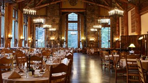 Tall dining room with open beams, high windows, and chandeliers.