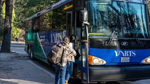Two passengers board a blue YARTS bus.