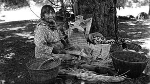 Maggie Howard, early Yosemite Indian, sitting among her baskets