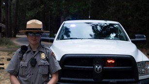 Law enforcement ranger standing in front of her vehicle.