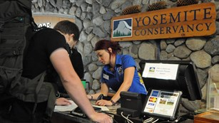 Yosemite Conservancy bookstore employee at the sales desk in Yosemite Valley at the visitor center.