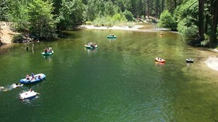 Visitors floating in rafts in the Merced River