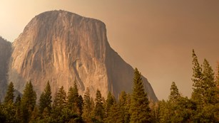 El Capitan rises through smoke from a wildfire