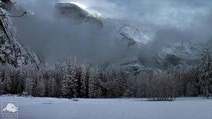 Snowy and cloudy view of Half Dome